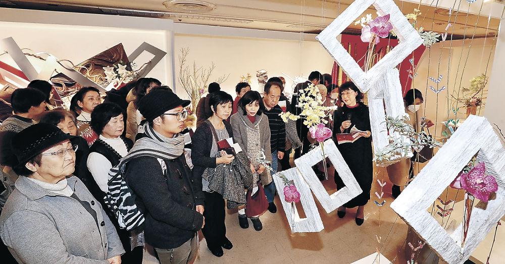 華道家のアイデアが詰め込まれた力作を鑑賞する来場者=金沢市のめいてつ・エムザ8階催事場