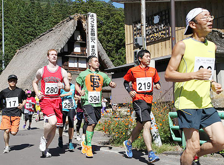 合掌造り家屋を背に五箇山路を駆ける世界遺産マラソン参加者。100キロマラニックでも同じような光景が見られる=2013年9月、南砺市上梨