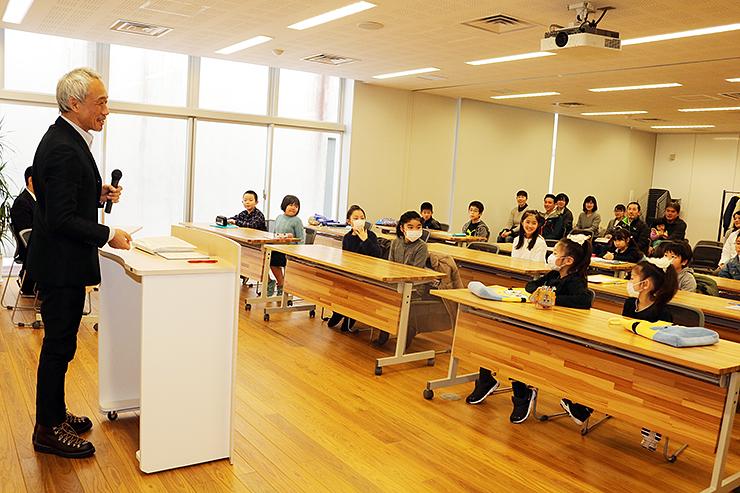 結団式で子どもたちを激励する西村さん(左)=高志の国文学館
