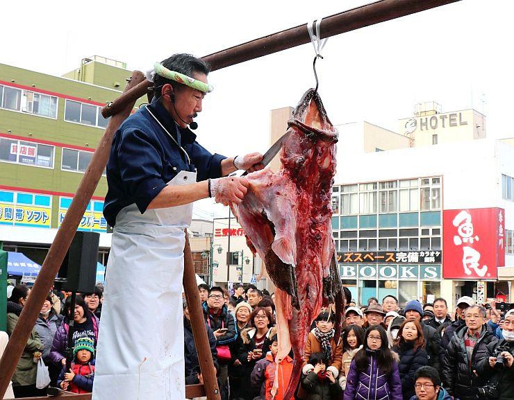 多くの人が見入ったアンコウのつるし切りの実演=21日、糸魚川市大町1の糸魚川駅日本海口前