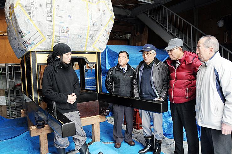 小原さん(左)から剱鉾の修復状況について説明を受ける新町の住民=城端地域中心部の収蔵庫