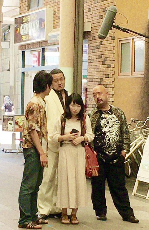 借金取りが女性に絡むシーンの撮影に臨む出演者。4人とも県内の劇団で活動している=昨年8月、富山市中央通り