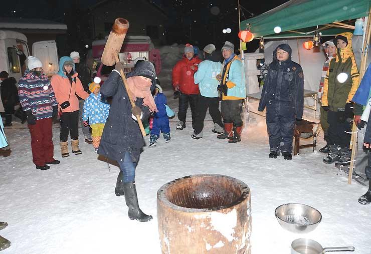 雪が降る中、観光客が順番に行った餅つき