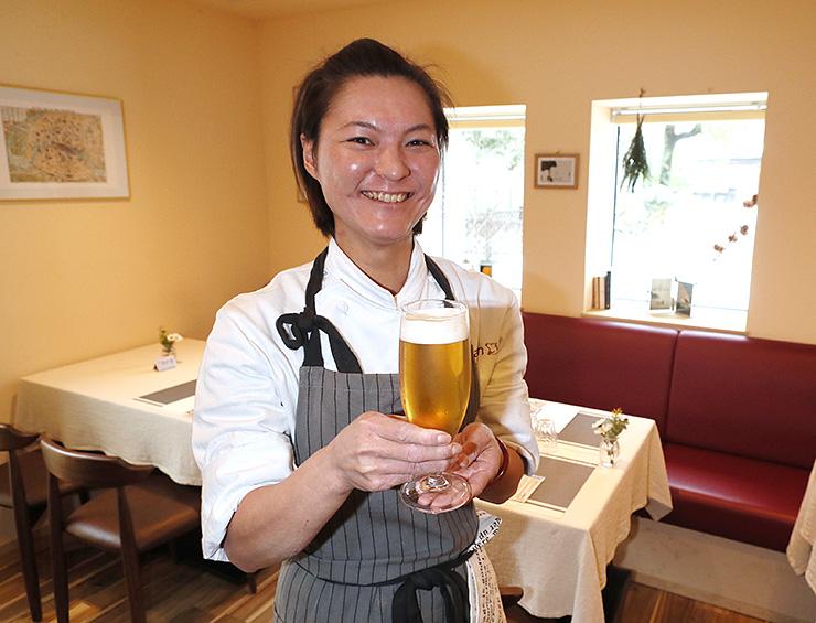 古里で開いた店で、はと麦ビールを手に笑顔を見せる新井さん