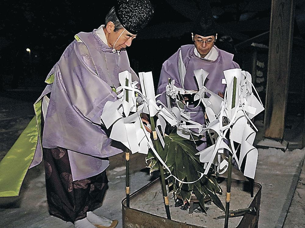 クマザサを湯釜の湯に浸す能門宮司(左)=輪島市河井町の重蔵神社