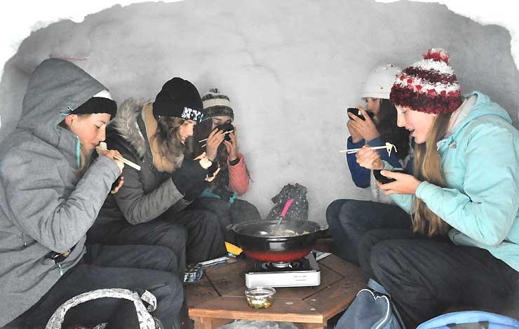 かまくらの中で鍋料理を味わうオーストラリアからの観光客