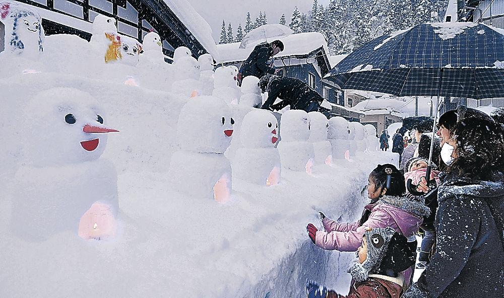 幻想的な灯りと多彩な雪だるまを楽しむ来場者=白山市桑島