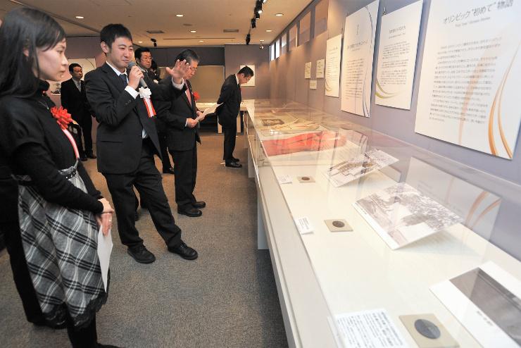 秩父宮記念スポーツ博物館学芸員の井上さん(左から2人目)から展示品の説明を聞く吉田さん(左端)ら