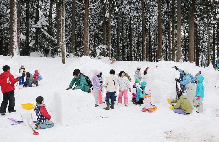 協力して雪の像を作る参加者=上市町東種