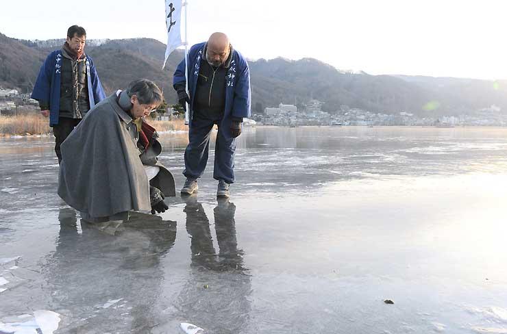下諏訪町の湖岸で氷の厚さを確認する宮坂宮司(右から2人目)ら