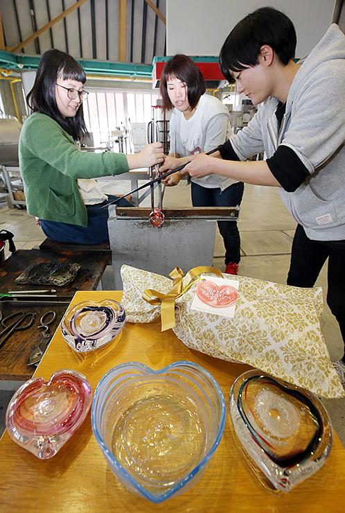 ハート形をしたガラスの器を作る女性たち=富山ガラス工房