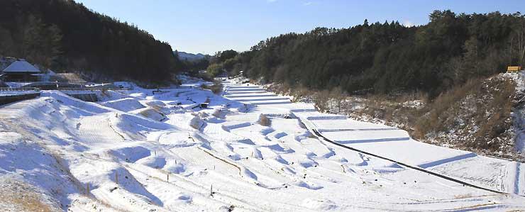 雪化粧して棚田の姿が浮かび上がった「よこね田んぼ」=29日、飯田市千代