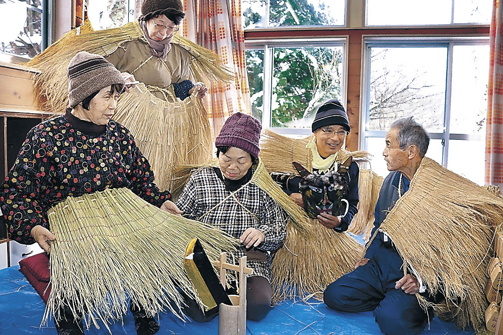 完成した衣装の出来栄えを確かめる住民=能登町秋吉公民館
