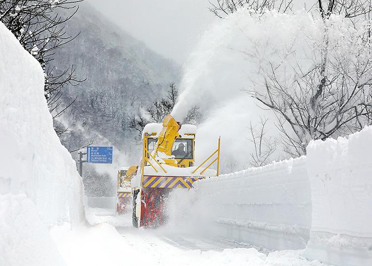高い雪の壁を削り取るロータリー車=立山町芦峅寺