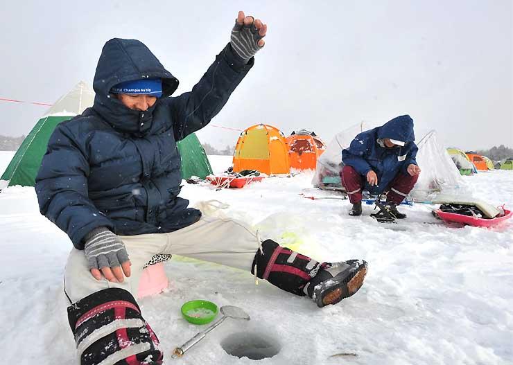凍った湖面に開けた穴からワカサギを釣り上げる池田さん=飯綱町の霊仙寺湖