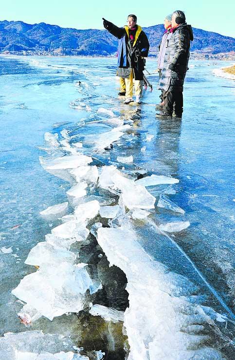 結氷した諏訪湖の上で、氷のせり上がりが大きくなってきた亀裂を確認する宮坂宮司(左)ら=31日午前8時16分、下諏訪町東赤砂