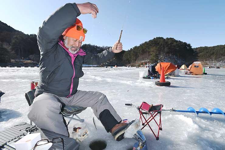 「これはちょっと大きめ」。美鈴湖でワカサギの穴釣りを楽しむ人たち=31日