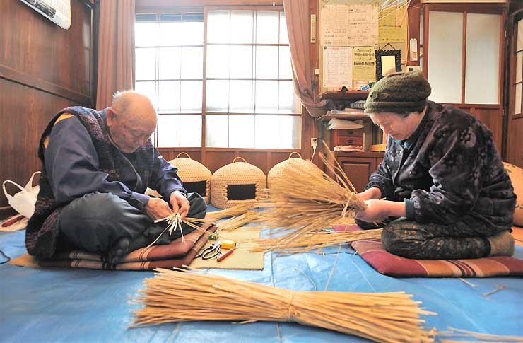 つぐらの材料となるわらを編む藤木金寿さん(左)と、わらを選別する妻のみちさん=栄村極野