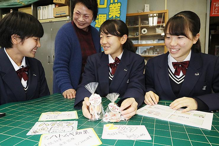 開発中の生キャラメルの試作品を手に、田悟さん(左から2人目)と打ち合わせる竹端さん(右)ら生徒=小矢部市役所