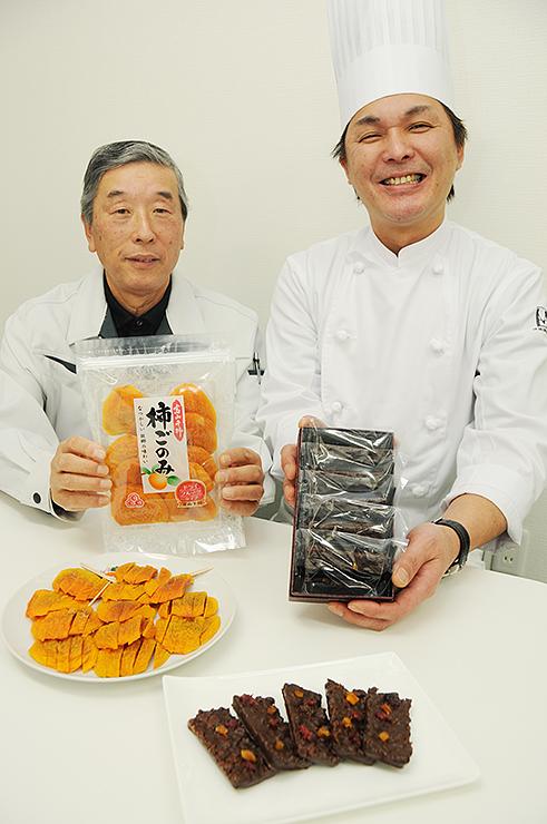 柿ごのみを使ったチョコレート菓子「カーキショコラ」を完成させた藤井幸治さん(右)=富山干柿出荷組合連合会
