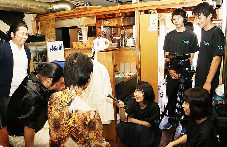 映画に出演した劇団員を取材する富山高校放送部員=昨年8月、富山市一番町