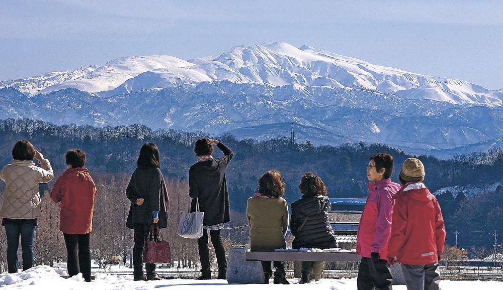 雪を頂く白山を眺める来園者=小松市の木場潟公園西園地