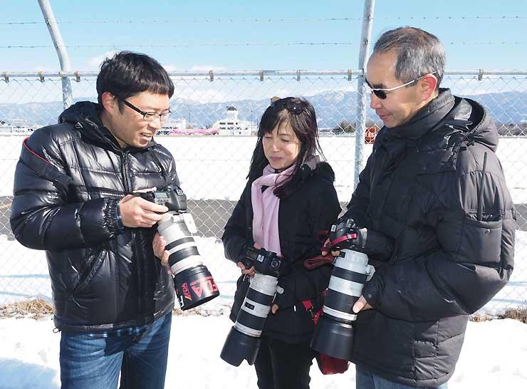 県営松本空港で撮影した写真を見せ合う斎藤さん(左)ら「FDAファンクラブ」のメンバーたち