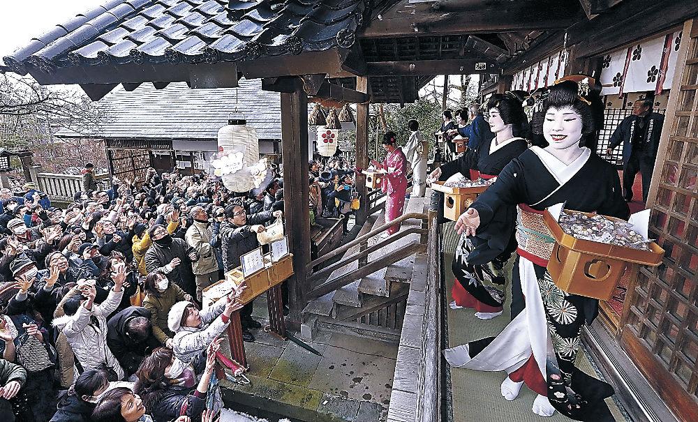 参拝客へ豆を投げる芸妓衆=金沢市東山1丁目の宇多須神社