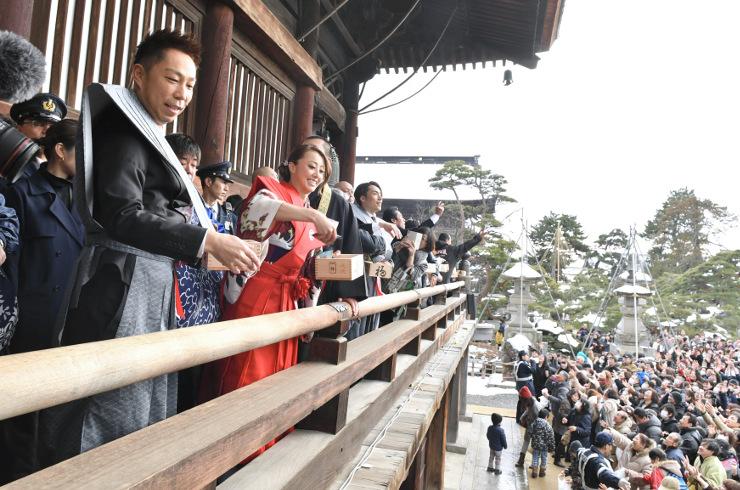 善光寺の境内に集まった参拝者に、本堂回廊から豆をまくウサさん(手前左)ら