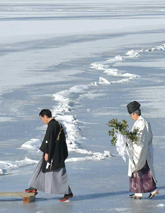 拝観式で、「一之御渡り」の近くを慎重に歩く八剣神社の宮坂宮司(右)と氏子=5日午前9時5分、下諏訪町西高木