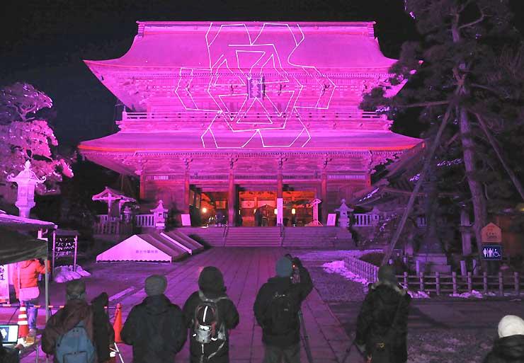 長野灯明まつりの試験点灯が行われた善光寺の山門=6日午後6時28分、長野市
