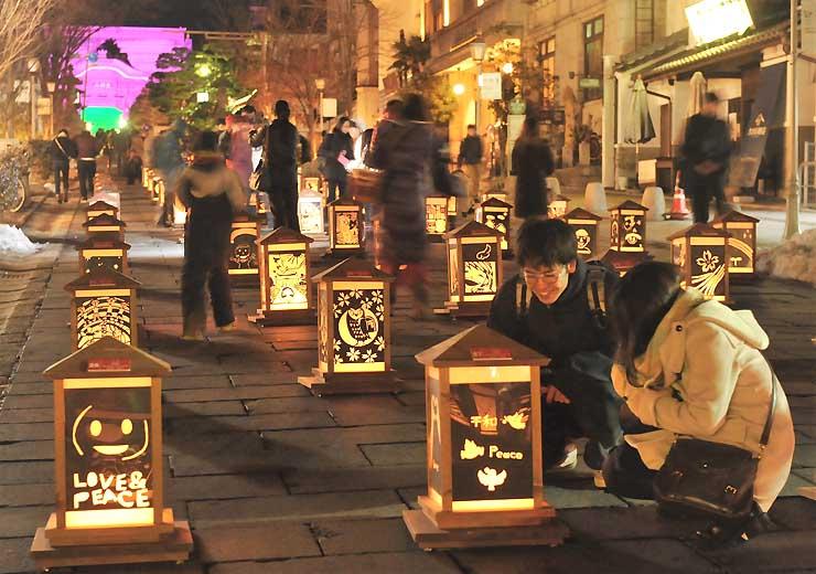 善光寺表参道に並んだ灯籠を見る人たち=7日午後7時45分、長野市