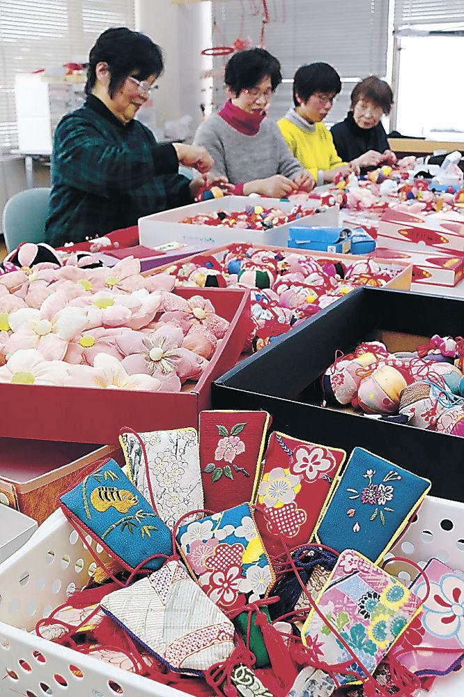 つるし飾りの準備を進める女性部員。今年は新たに羽子板の飾りが加わる=白山市の美川商工会館
