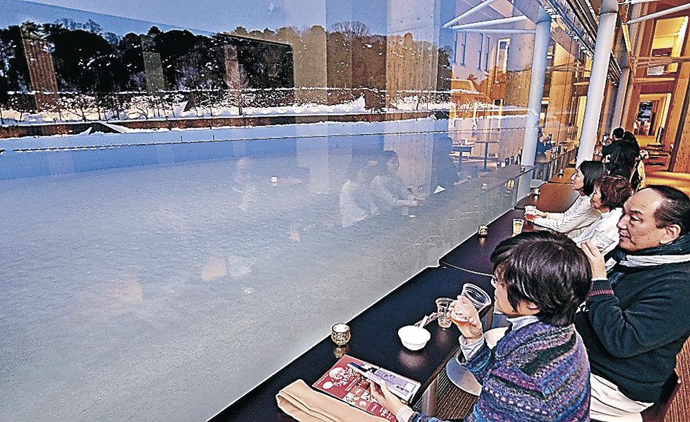 雪景色や石垣を眺めながら飲食を楽しむ来場者=金沢市のしいのき迎賓館