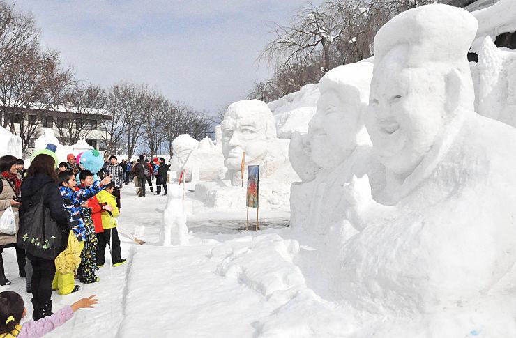 右から北朝鮮の金正恩・朝鮮労働党委員長、米国のトランプ大統領、西郷隆盛を模した雪像が並んだ、いいやま雪まつりの会場