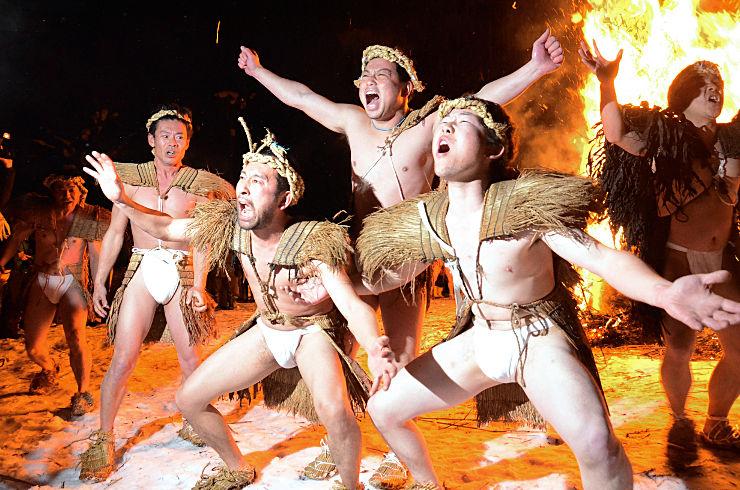 炎の前で雄たけびを上げる男衆