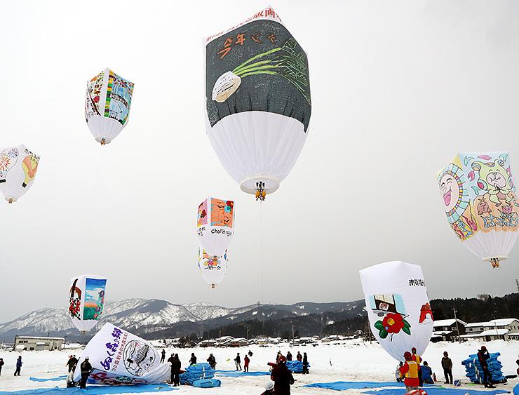 医王山の山並みを背景に冬空に揚がる巨大紙風船=道の駅福光