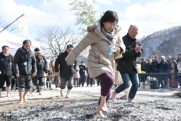 灰の上を速足で通り過ぎる人たち