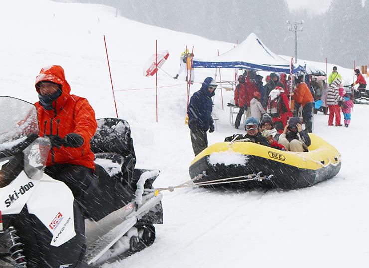 「雪上ラフティング」を楽しむ家族連れ