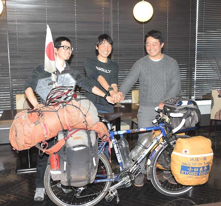 協議会設立を発表した小口良平さん(中)と小口正史さん(右)、米田信吾さん。良平さんが世界一周で使用した自転車も披露した
