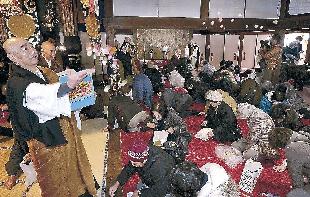僧侶がまく涅槃団子を求める檀信徒=金沢市長坂町の大乘寺