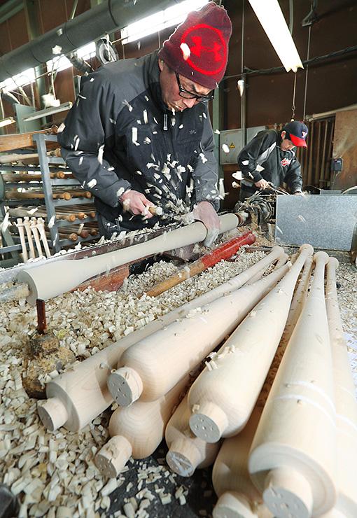 高速回転させた木材を削り、バットを作る職人=エスオースポーツ工業(写真部部長デスク・垣地信治)