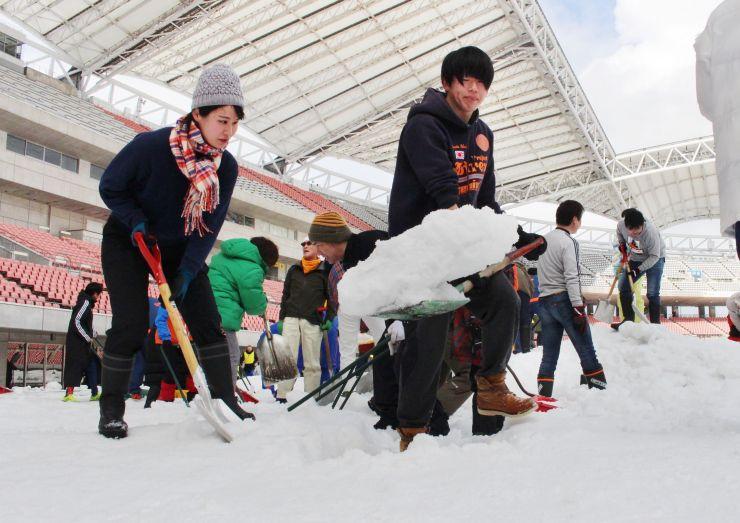 スタジアムの除雪ボランティアに参加したアルビレックス新潟のサポーターら=18日、新潟市中央区のデンカビッグスワンスタジアム