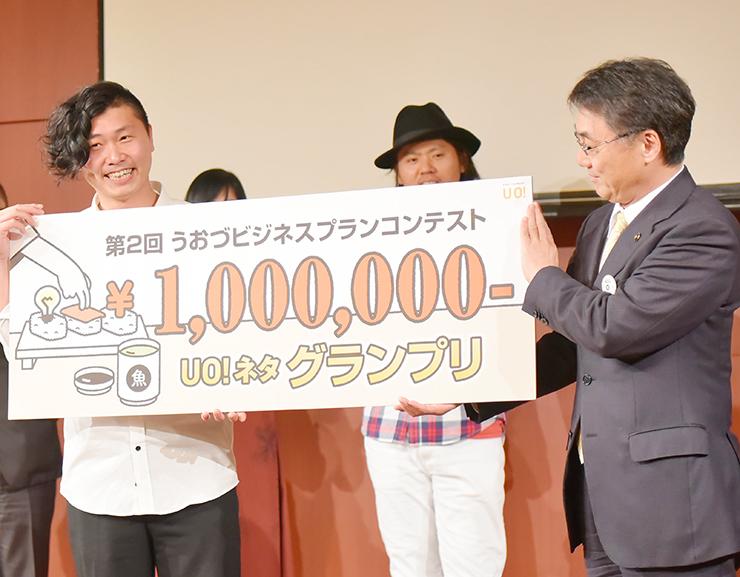 村椿市長からグランプリのボードを受け取った窪田さん(左)