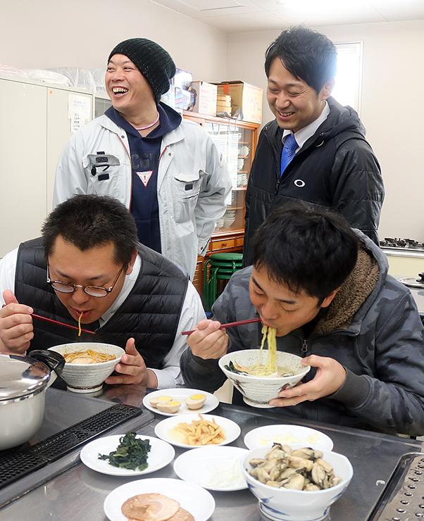 ブラウンラーメンと牡蠣ラーメンを試食し笑顔を見せる善商メンバー=うるおい館