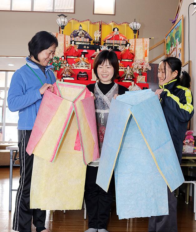 和紙製の装束を手に、イベントを楽しみにする横谷さん(中央)と奥野さん(左)、宮内さん=谷口公民館