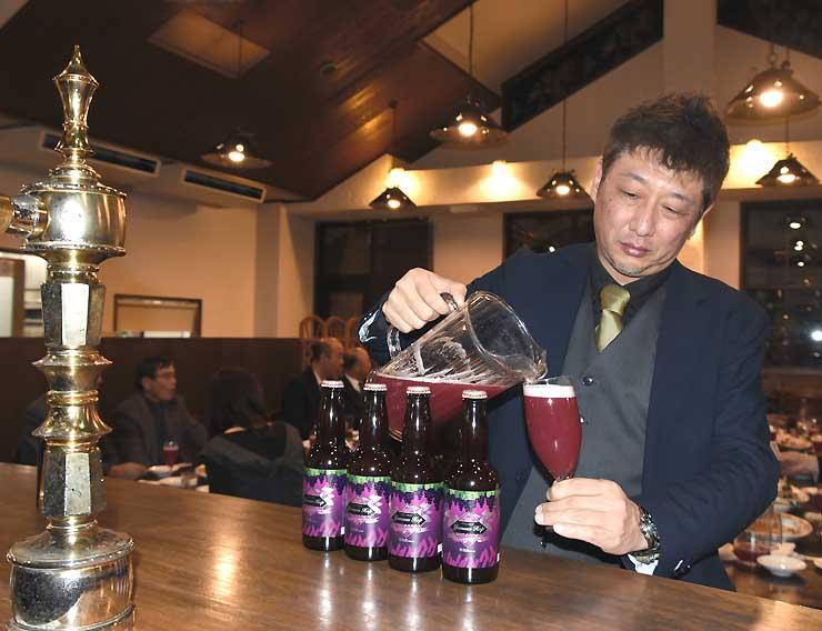 赤紫の液体とピンクの泡が特徴の「ヤマソーホップ」をグラスに注ぐ竹平さん