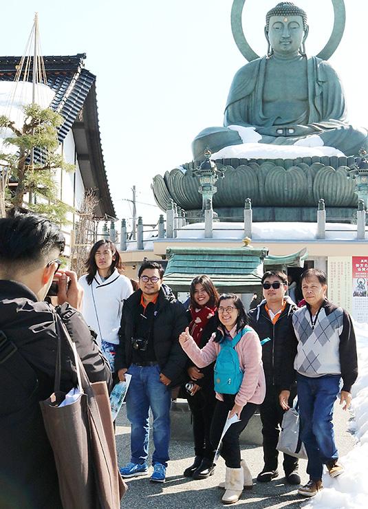 高岡大仏の前で記念撮影するタイの旅行客