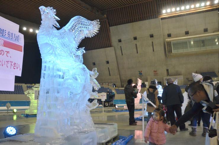 ライトアップされた氷の彫刻を見上げる来場者たち