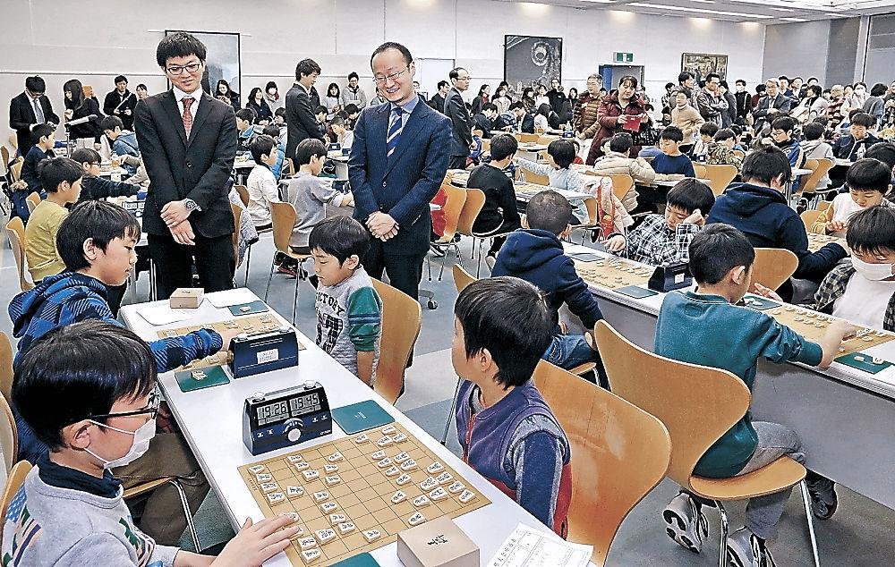 子どもたちの対局を見守る渡辺棋王(右)と永瀬七段=北國新聞20階ホール